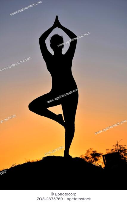 Silhouette of young girl in yoga pose near mountain, Pune, Maharashtra