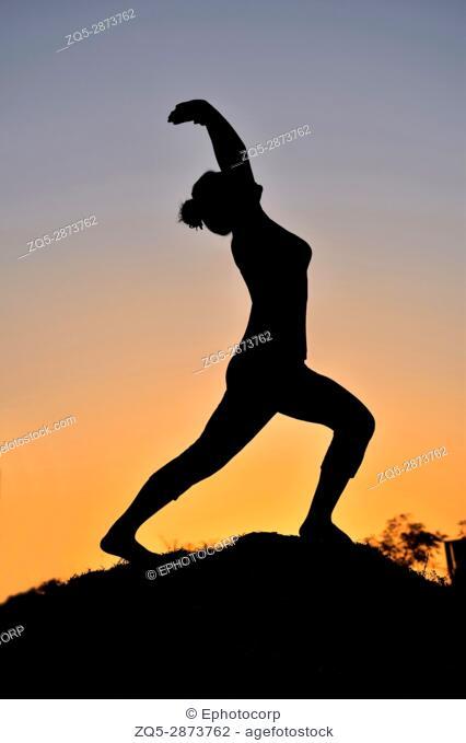 Silhouette of young girl in virabhadrasana warrior pose near mountain, Pune, Maharashtra